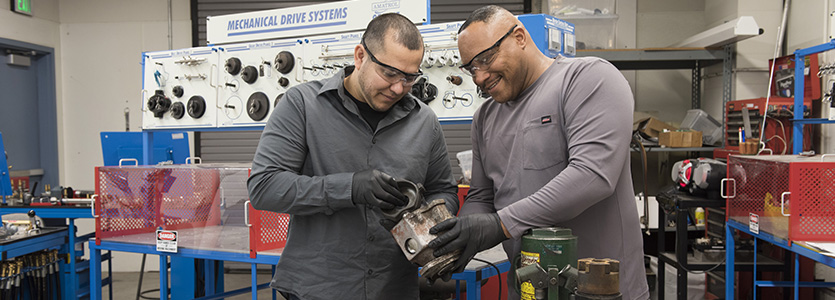 two men working with a part